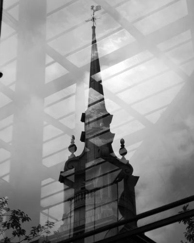 Steeple Reflection: Old church steeple through the window of modern office block in London, UK.