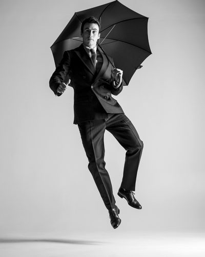 Umbrella Heels: Actor Huw Collins showing the bright side of the british weather with his happy heel click holding an umbrella. One of a series submitted for consideration to be included in the 'American Photography' Book